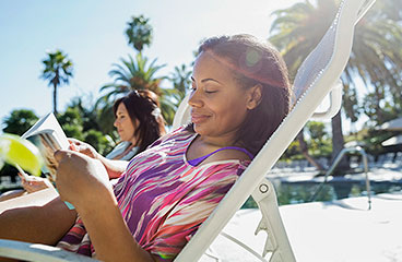 An image of a woman reading a book in a lounge chair on a beach.