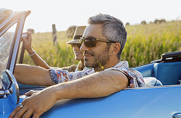 An image of a couple driving in a convertible.