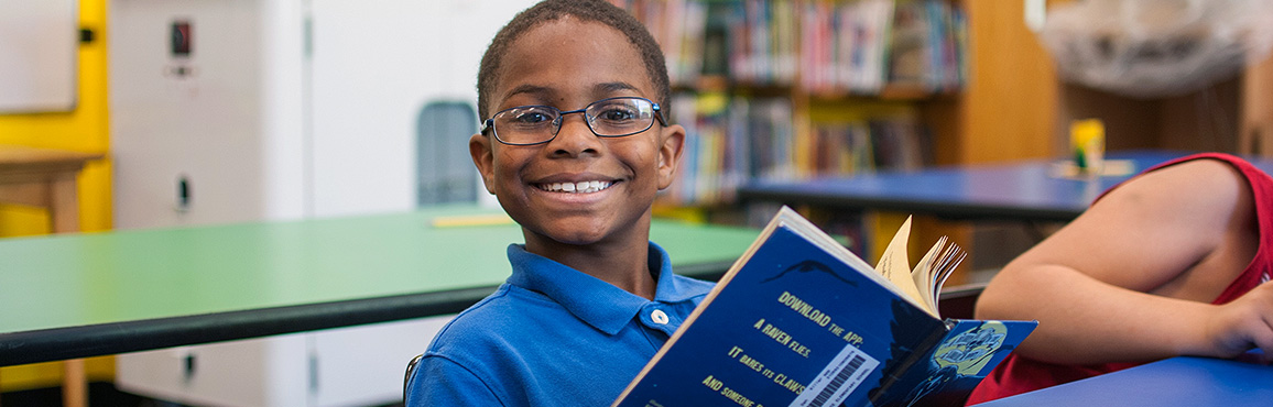 Child looks up from his book to smile at the camera.