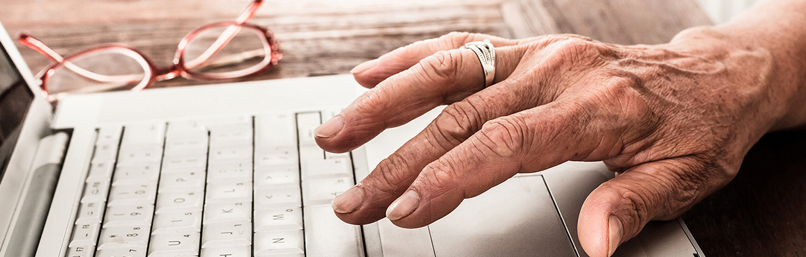 Elderly hands typing on a keyboard.