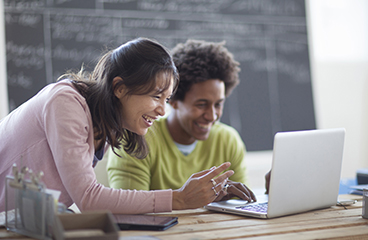 Young people laughing over a computer.