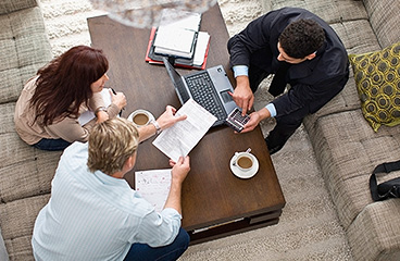 Three people sitting around a coffee table.