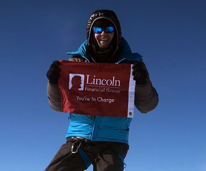 Jeff Glasbrenner holding a Lincoln Financial Group flag on the top of Mount Vinson.