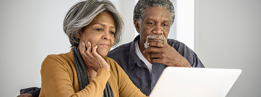 An older couple looking at a computer.