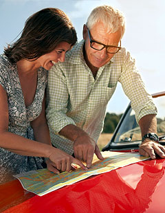 Lost middle aged couple looking at a map on the hood of their red convertible