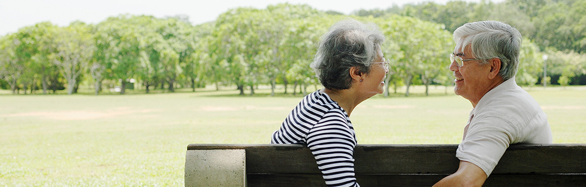 Elderly couple staring lovingly into each other's eyes while sitting on a park bench