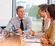 Three people in business attire sitting at a table