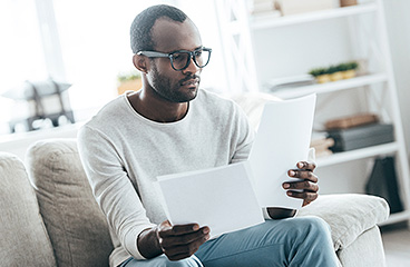 Man sitting on a couch and going through paperwork