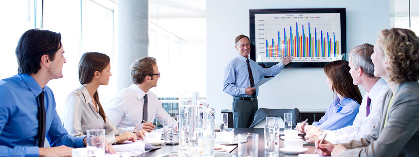 Man presenting a chart to a room full of business people