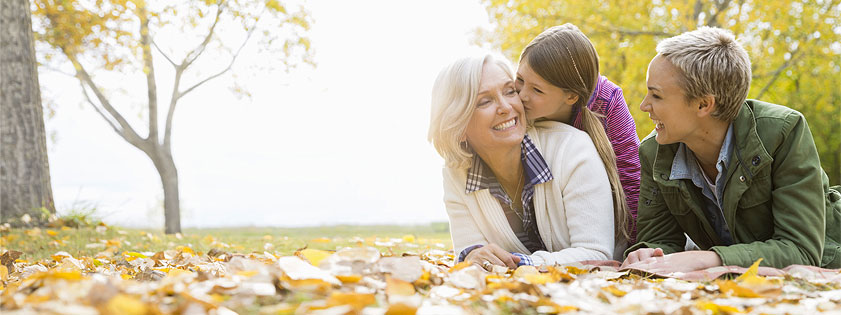 Grandmother, mother, and young daughter laughing in a pile of leaves