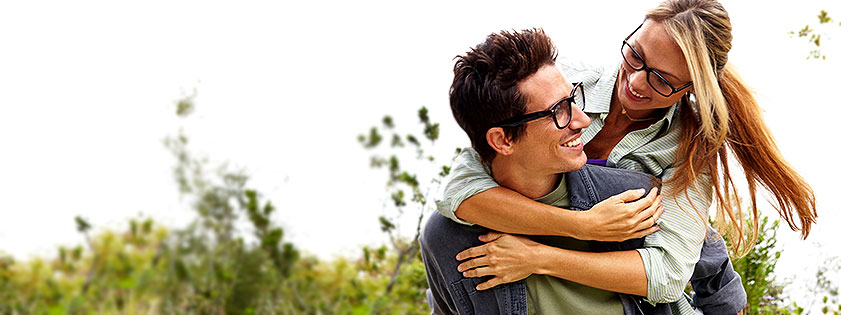A bespectacled young man giving a bespectacled young woman a piggyback ride