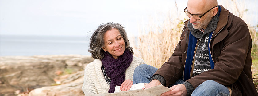 Middle-aged couple looking at a map on a beach
