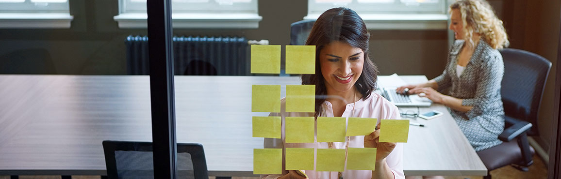 Businesswoman placing sticky notes on a glass window