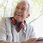 Middle-aged man wearing headphones and smiling