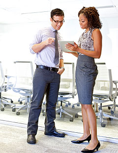 Man and lady wearing professional attire in a business setting.