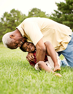 Grandfather hugging his grandson on the lawn