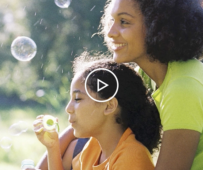 Mother and young daughter blowing bubbles