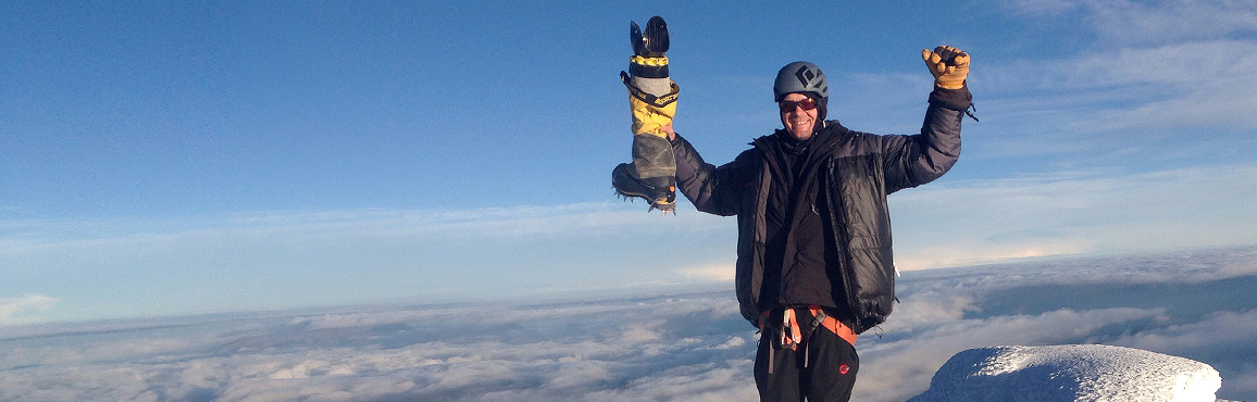Jeff Glasbrenner celebrating on top of a mountain and holding up his prosthetic leg