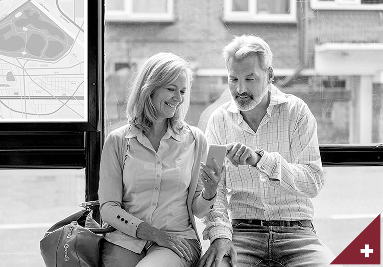 Two people sitting and looking at a cell phone.