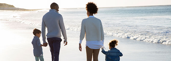 Family walking on a beach Image