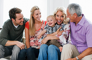 Multi generational family sitting and smiling.