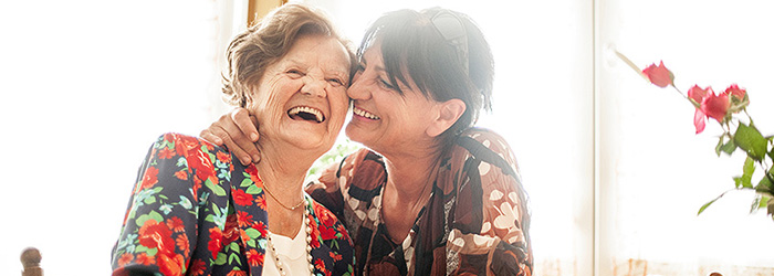 Middle aged woman and her elderly mother smiling