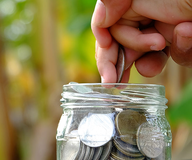 A hand putting a coin into a jar full of coins.