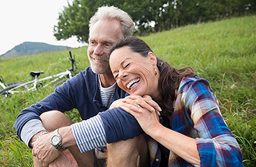 Couple sitting on the grass laughing