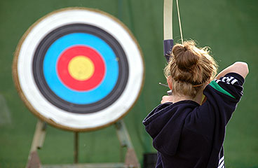 A woman aiming at a target with a bow and arrow