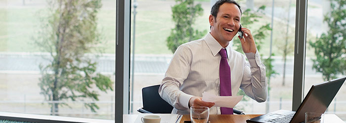 Happy businessman on a business call holding business papers