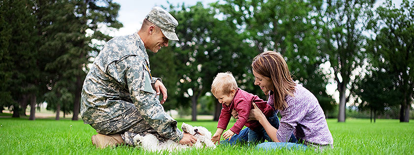 Man in military uniform playing with his young family