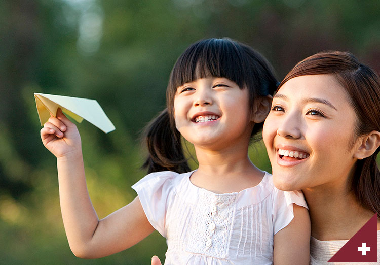 Mother and daughter playing with a paper airplane