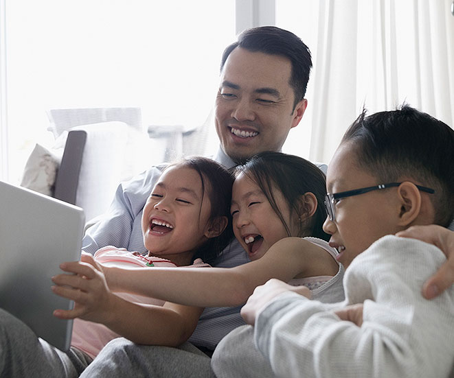 Dad and 3 kids laughing while looking at a tablet