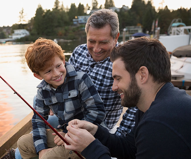 A father and grandfather teaching the son to fish.