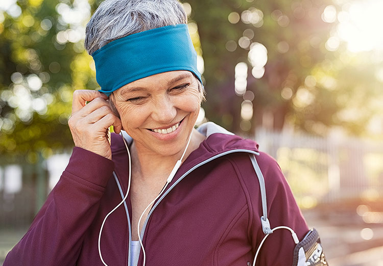 Smiling woman with headphones wearing a turquoise headband