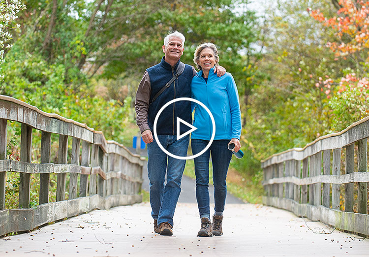 Man and woman walking shoulder to shoulder on a bridge in the woods