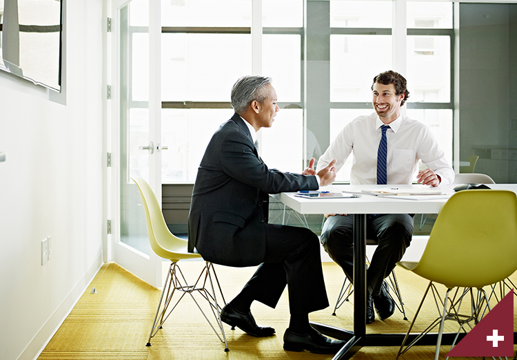 Two coworkers discussing project in office conference room smiling