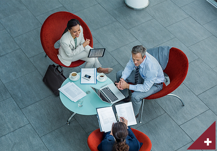 High angle view of 3 business people discussing strategy at coffee table in office